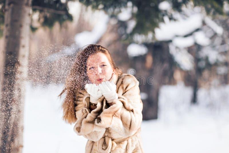 Nieve que sopla de la mujer hermosa joven en invierno foto de archivo libre de regalías