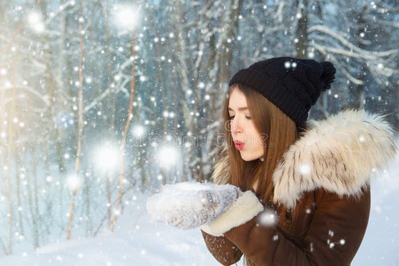 Nieve que sopla de la mujer Mujer joven en el invierno Retrato de la mujer joven del invierno Mujer joven hermosa que ríe al aire foto de archivo libre de regalías