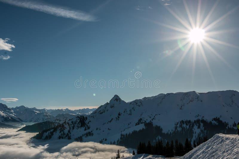 Nieve y sol en el top de las montañas y de la niebla abajo del valle foto de archivo