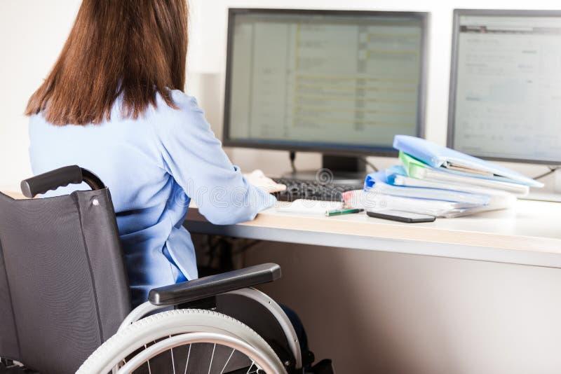 Nieważnej lub niepełnosprawnej kobiety siedzący wózek inwalidzki pracuje biurowego biurka komputer obrazy royalty free