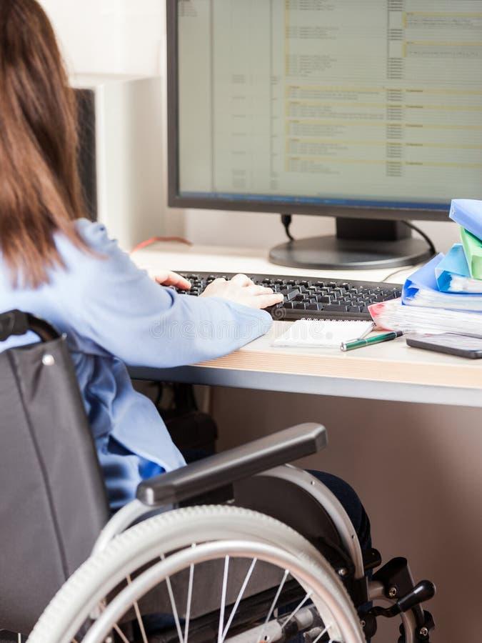 Nieważnej lub niepełnosprawnej kobiety siedzący wózek inwalidzki pracuje biurowego biurka komputer zdjęcie royalty free