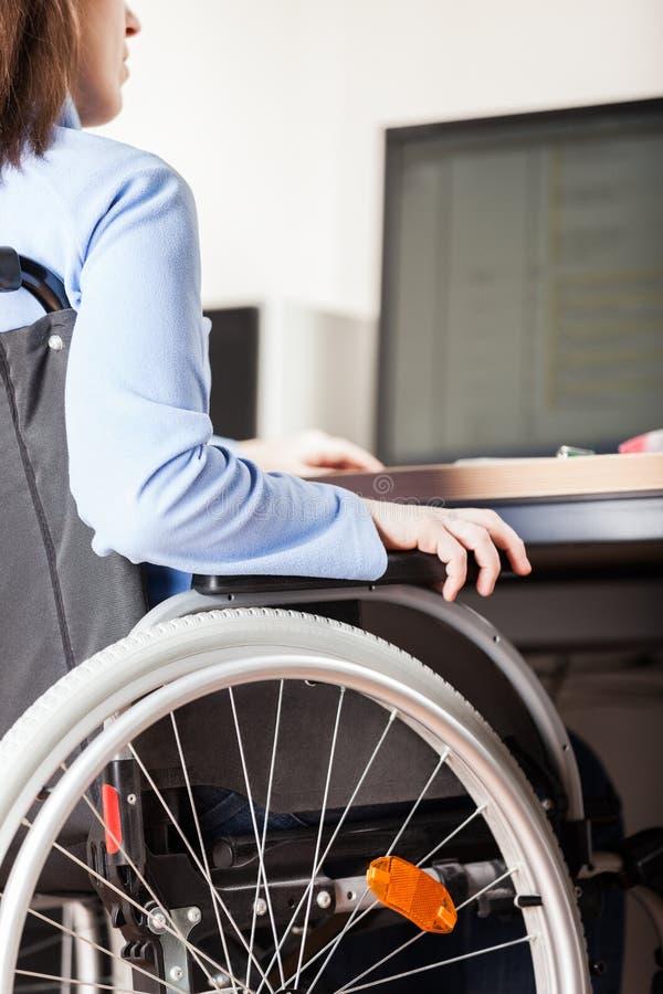 Nieważnej lub niepełnosprawnej kobiety siedzący wózek inwalidzki pracuje biurowego biurka komputer zdjęcia stock