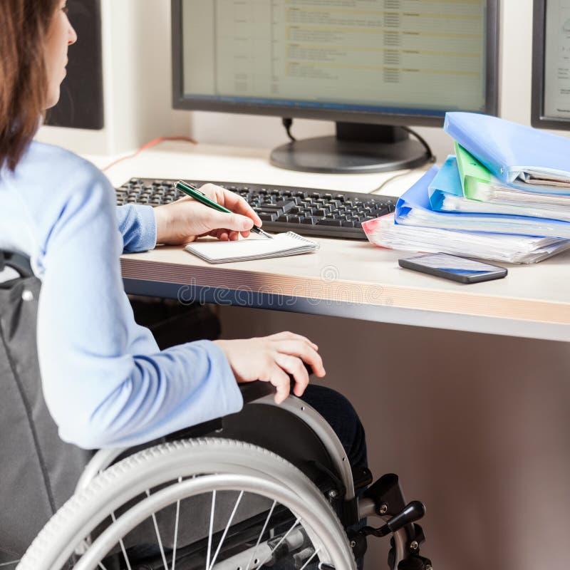 Nieważnej lub niepełnosprawnej kobiety siedzący wózek inwalidzki pracuje biurowego biurka komputer zdjęcia royalty free