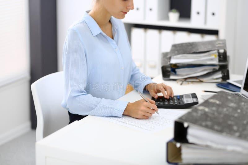 Niewiadoma żeńska księgowa, pieniężny inspektorski cyrklowanie lub sprawdzać równowaga, robi raportowi, zakończenie wewnętrzny fotografia royalty free