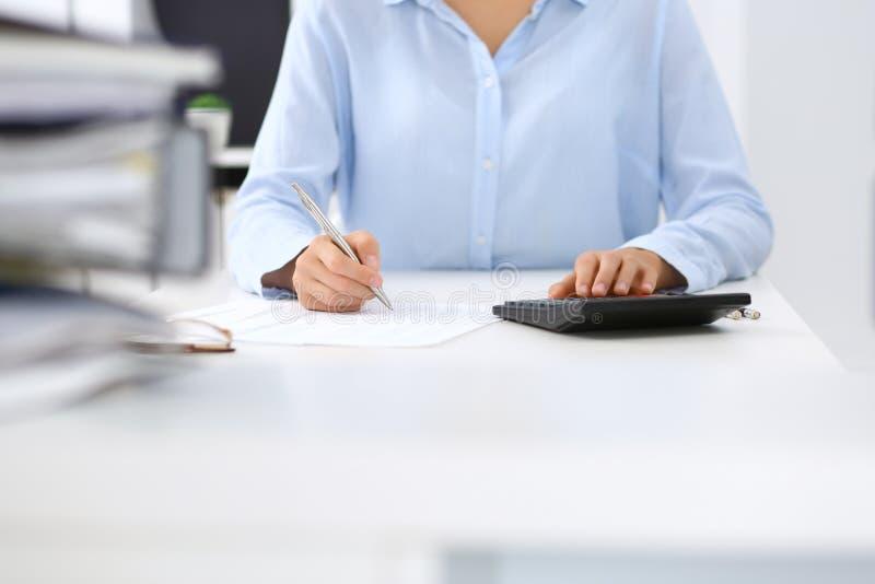 Niewiadoma żeńska księgowa, pieniężny inspektorski cyrklowanie lub sprawdzać równowaga, robi raportowi, zakończenie wewnętrzny obraz stock