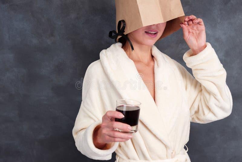 Niewiadoma dama jest ubranym bathrobe z zamkniętą twarzą pije alkohol zdjęcia stock