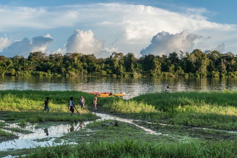 Niewiadoma dziecko sztuka na brzeg rzeki blisko wioski, Zmierzch, końcówka dzień Czerwiec 26, 2012 w wiosce, Nowa gwinea, Indonez obraz royalty free
