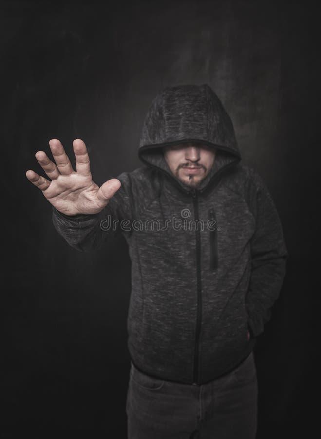 Niewiadomy mężczyzna wskazuje ręcznie na zmroku w kapiszonie Ostro?? na r?ce obrazy stock