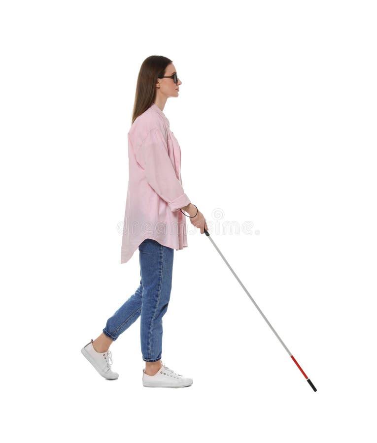 Niewidoma kobieta z długą trzciną na bielu fotografia stock