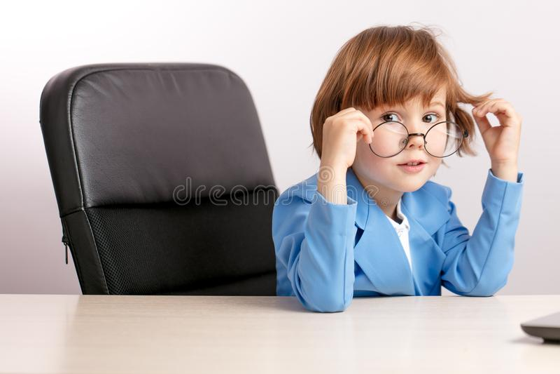 Niewinnie dzieciak siedzi w biurze zdjęcia stock