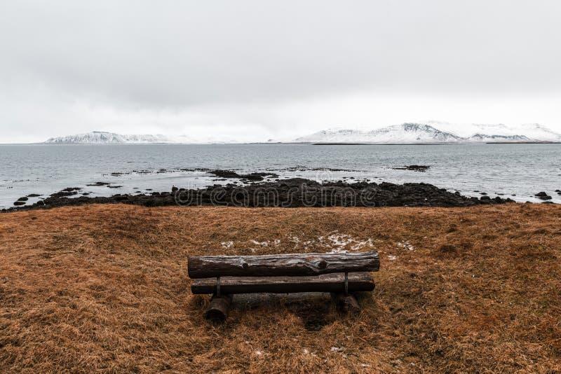 Niezły widok na morze i góry z drewnianą ławką w Reykjaviku, Islandia obraz stock