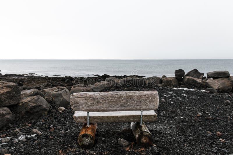 Niezły widok na morze z drewnianą ławką w Reykjaviku, Islandia obrazy stock