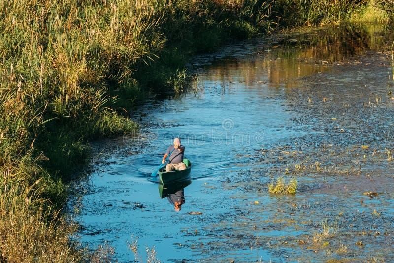 Niezdefiniowany mężczyzna połów Od Starej Drewnianej łodzi rybackiej W Lato jeziorze zdjęcie stock