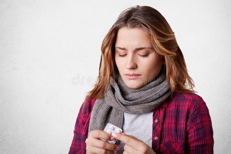 Niezdrowa ładna kobieta trzyma pigułki, bierze medycynę, próby niska temperatura, lekarstwa od złego zimna nad białym backgroun, zdjęcia royalty free