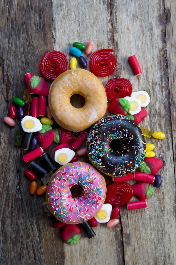 Niezdrowa ale wyśmienicie grupa słodcy cukrowi pączków torty i udziały gumowaci cukierki na rocznika drewnianym stole fotografia stock