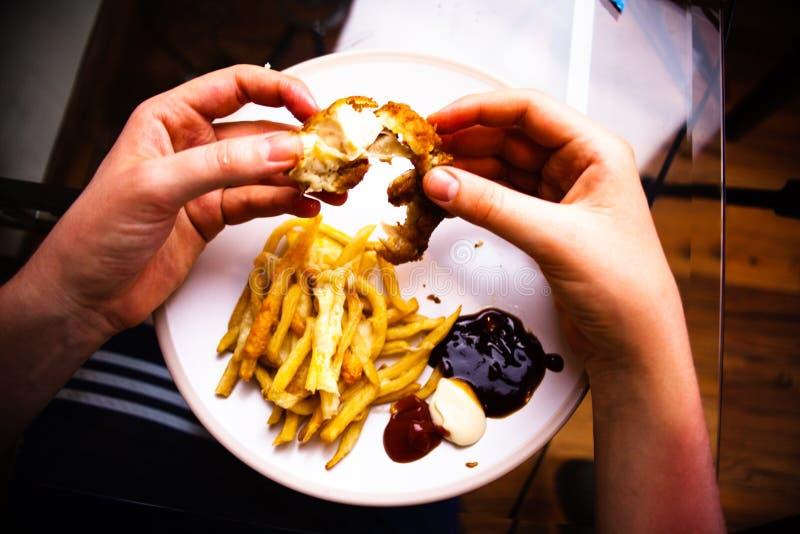 Niezdrowy łasowanie fasta food pojęcie Mężczyzna trzyma kurczaki smażących skrzydła w jego rękach Łasowanie posiłek z rękami Wyśm fotografia stock