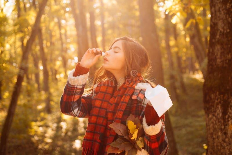 Niezend jong meisje met neuswisser onder gele bomen in park De vrouw maakt een behandeling voor de verkoudheid Het tonen van ziek stock afbeeldingen
