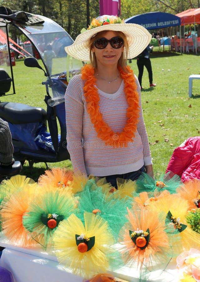 Niezidentyfikowana Ładna kobieta z białym kapeluszem pozuje przy Pomarańczowym okwitnięcie karnawałem zdjęcia royalty free