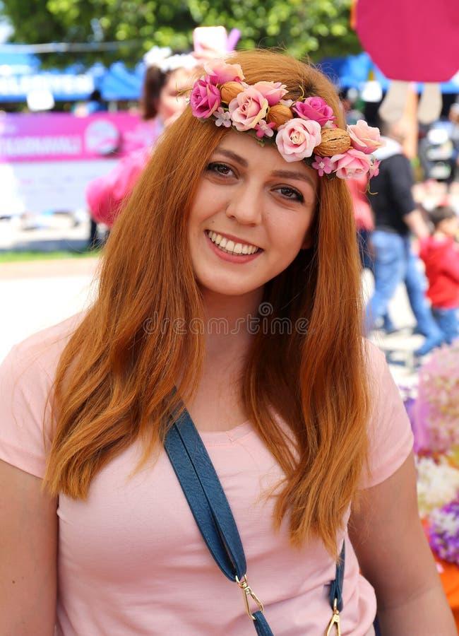 Niezidentyfikowana Ładna kobieta z dużym uśmiechem pozuje przy Pomarańczowym okwitnięcie karnawałem obraz stock