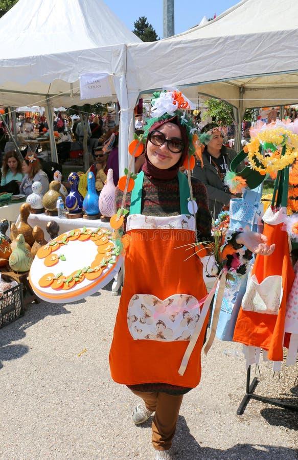 Niezidentyfikowana Ładna kobieta z pomarańczowym fartuchem i hijab pozuje przy Pomarańczowym okwitnięcie karnawałem zdjęcia stock