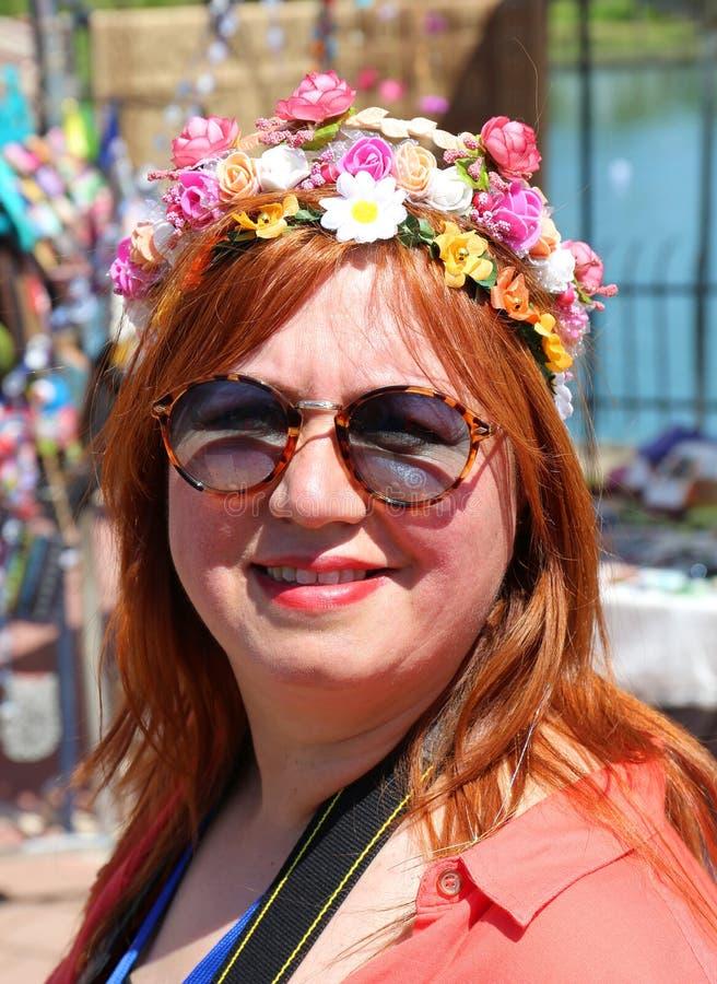 Niezidentyfikowana Ładna kobieta z uśmiechem i okularami przeciwsłonecznymi pozuje przy Pomarańczowym okwitnięcie karnawałem zdjęcia stock