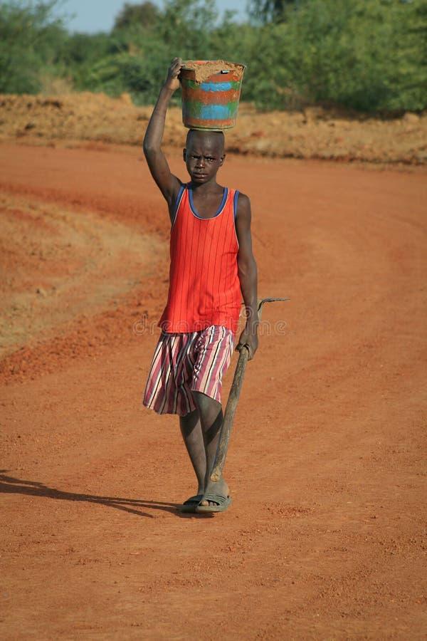 Niezidentyfikowana chłopiec przewożenia glina w drewnianym naczyniu na jego głowie zdjęcie royalty free