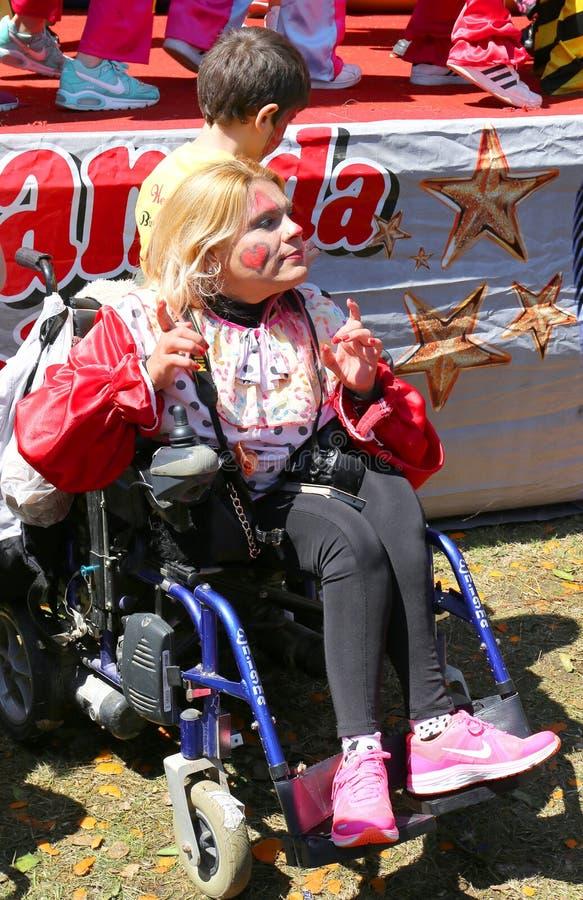 Niezidentyfikowana kobieta na koła krześle ma zabawę przy Pomarańczowym okwitnięcie karnawałem zdjęcia royalty free
