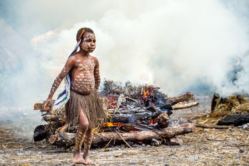 Niezidentyfikowana mała dziewczynka Dugum Dań plemię jest blisko ogienia w dymu zdjęcie stock