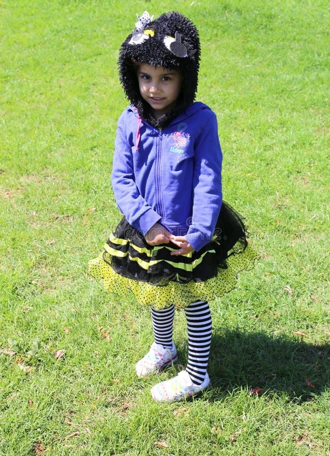 Niezidentyfikowana Nieśmiała mała dziewczynka z pszczoła kostiumem pozuje przy Pomarańczowym okwitnięcie karnawałem zdjęcie royalty free