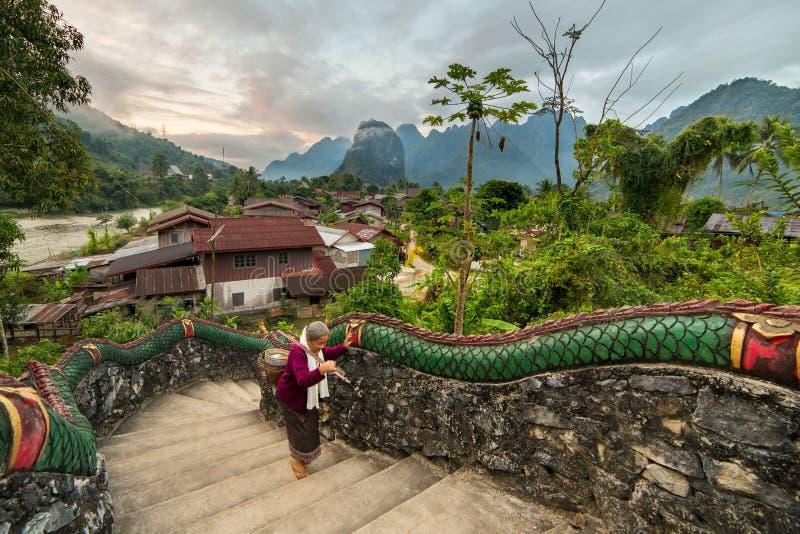Niezidentyfikowana starsza kobieta chodzi w górę świątynnych schodków z pięknym wiejskim krajobrazem na tle w Vang Voeng, Laos fotografia stock