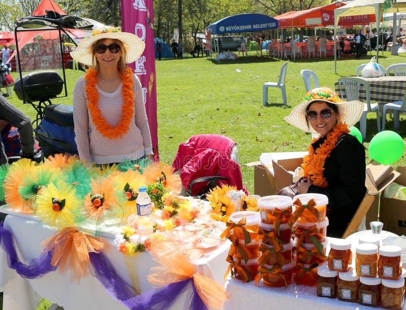Niezidentyfikowane Ładne kobiety z kapeluszowego sprzedawania pomarańczowym dżemem i kwiatami przy Pomarańczowym okwitnięcie karn obraz stock