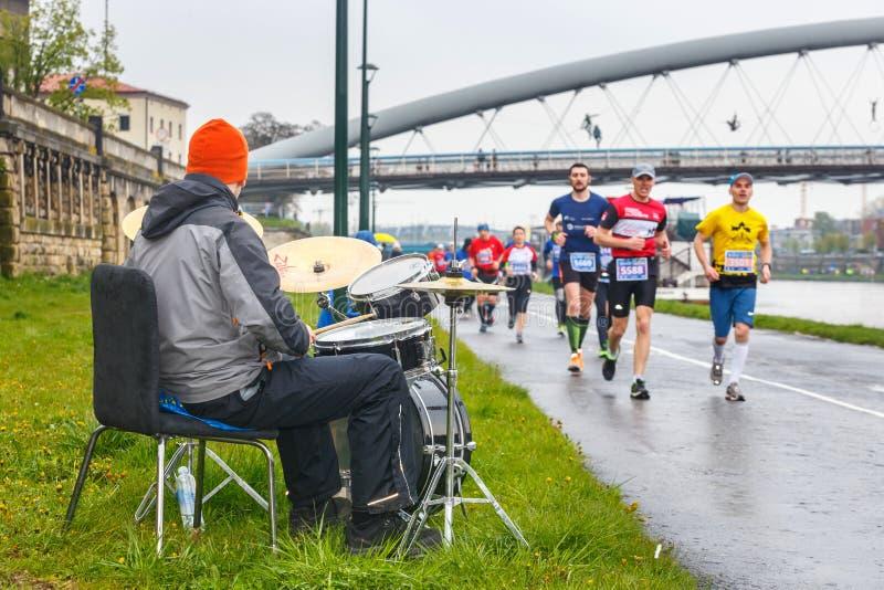 Niezidentyfikowanego dobosza podporowi biegacze podczas 16 Cracovia maratonu obrazy royalty free