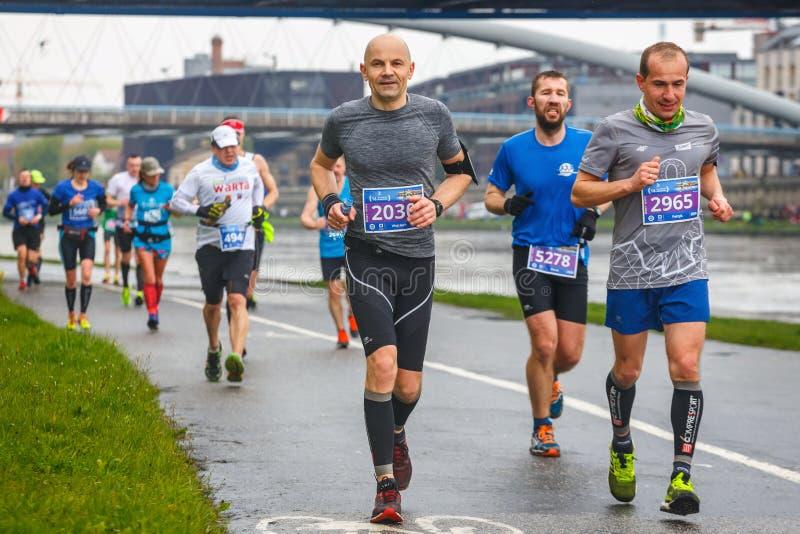 Niezidentyfikowani biegacze na ulicie podczas 16 Cracovia maratonu obraz stock