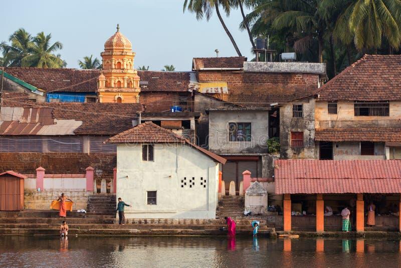 Niezidentyfikowani indyjscy ludzie kąpać się w świętym jeziorze w Gokarna Miasto jest świętym pielgrzymki miejscem dla Hinduists obraz royalty free