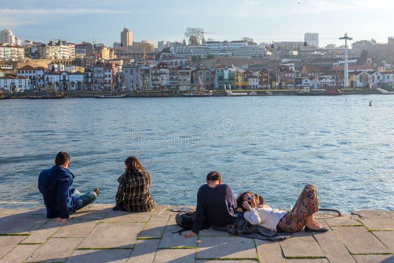 Niezidentyfikowani ludzie odpoczywają na Douro brzeg rzekim przy słonecznym dniem w Porto, Portugalia fotografia stock