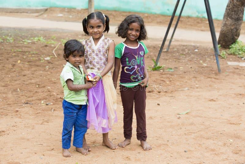Niezidentyfikowani szczęśliwi wiejscy biedni dziecko nastolatkowie bawić się przy ulicą wioska obrazy royalty free