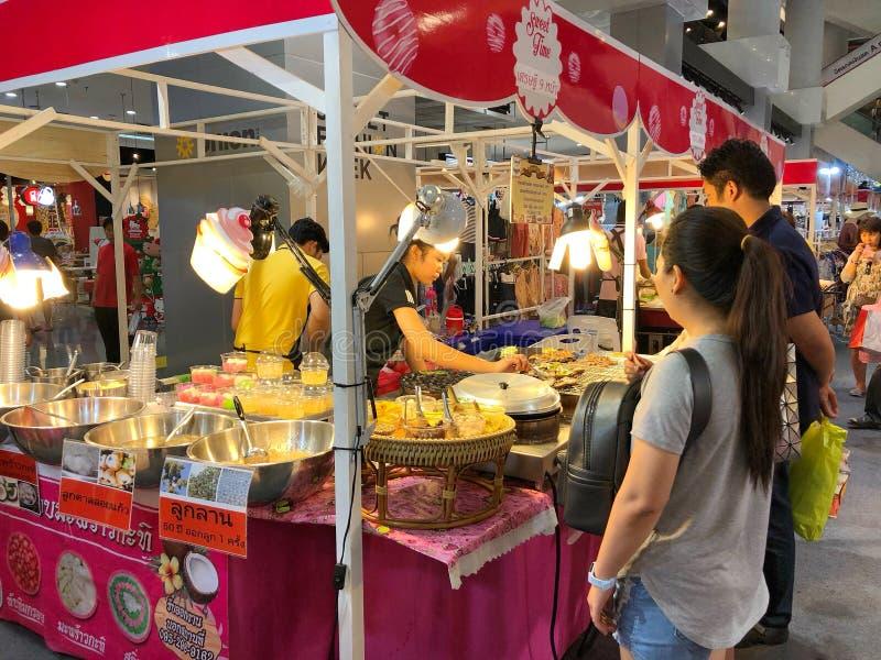 Niezidentyfikowani turyści czeka zakup przy Zrzeszeniowym centrum handlowym na Ladprao drodze niektóre jedzenie obrazy royalty free