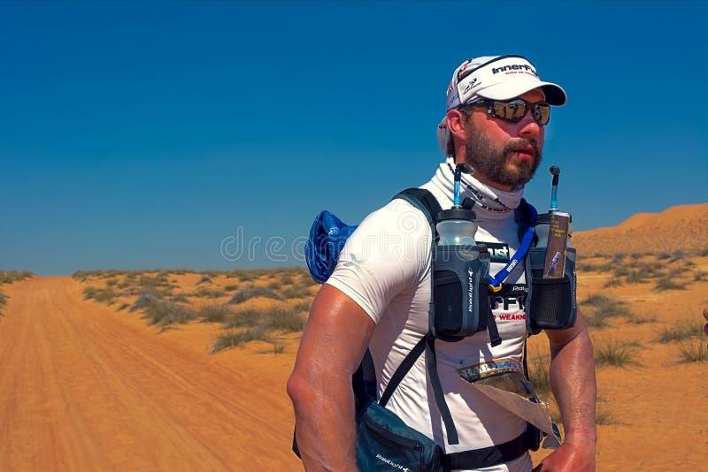 Niezidentyfikowany biegacz odpoczywa po pierwszej fazy biega Transomania pustynna wytrzymałość obraz stock