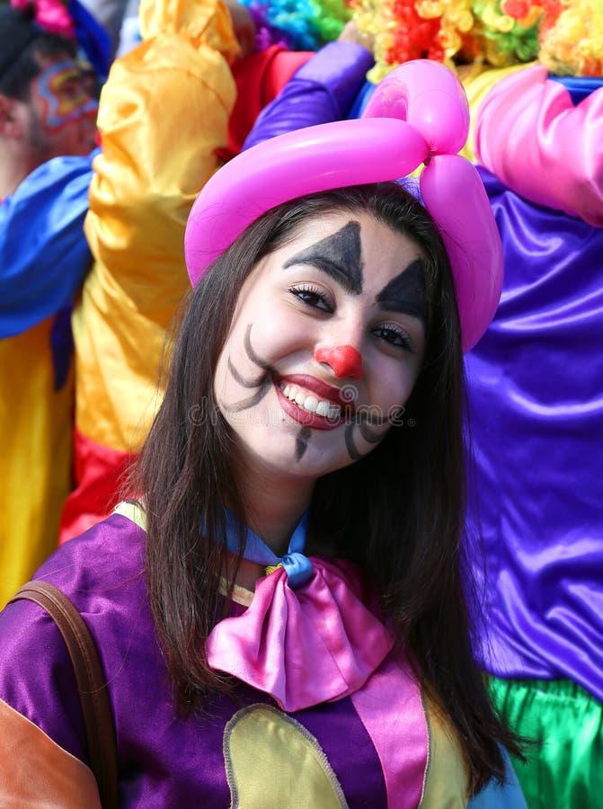 Niezidentyfikowany dziewczyna błazen z dużym uśmiechem pozuje przy Pomarańczowym okwitnięcie karnawałem obraz stock