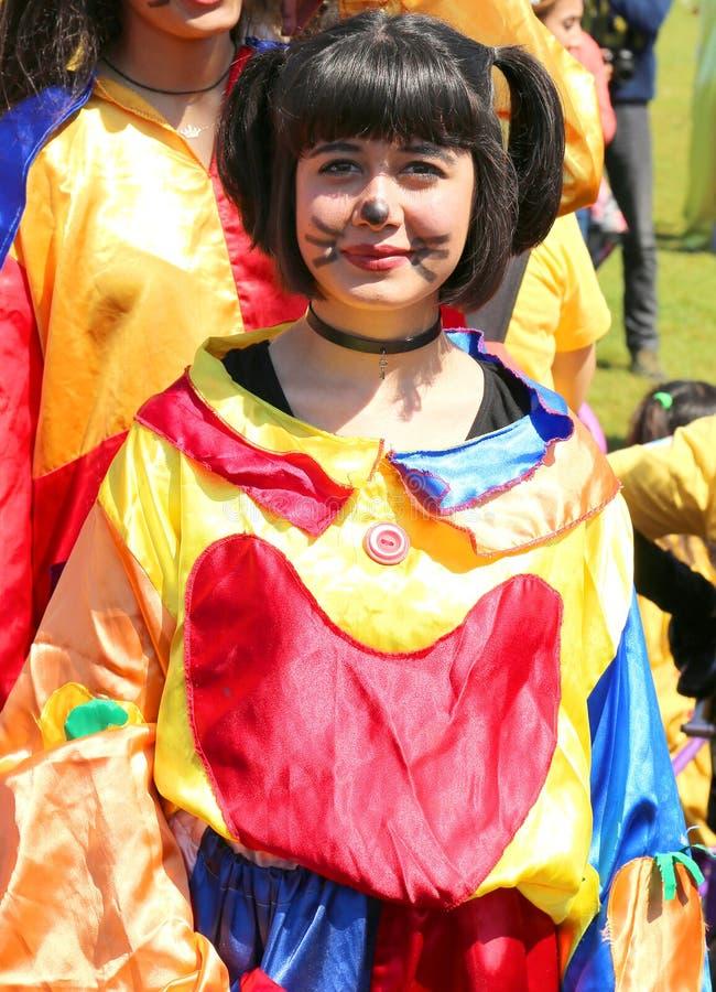 Niezidentyfikowany dziewczyna błazen z dużym uśmiechem pozuje przy Pomarańczowym okwitnięcie karnawałem obrazy royalty free
