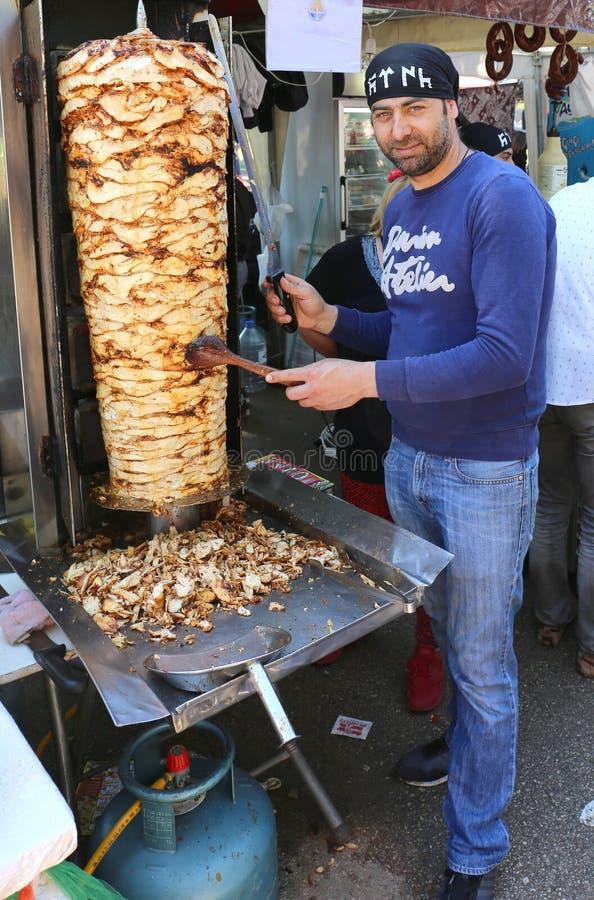 Niezidentyfikowany faceta przecinania kurczak Doner Kebab z kordzikiem jak długi nóż obrazy stock
