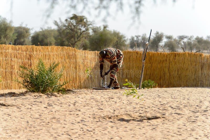 Niezidentyfikowany Fulani mężczyzna w barwionych kostiumów chyłach zestrzela woda zdjęcia stock