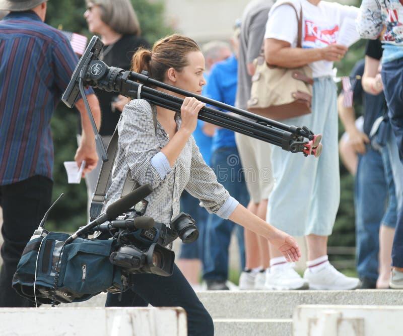 Niezidentyfikowany kobieta reportera przewożenia kamery wyposażenie zdjęcia stock
