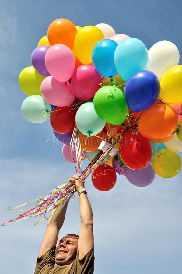 Niezidentyfikowany mężczyzna trzyma wiązkę stubarwni balony obraz royalty free