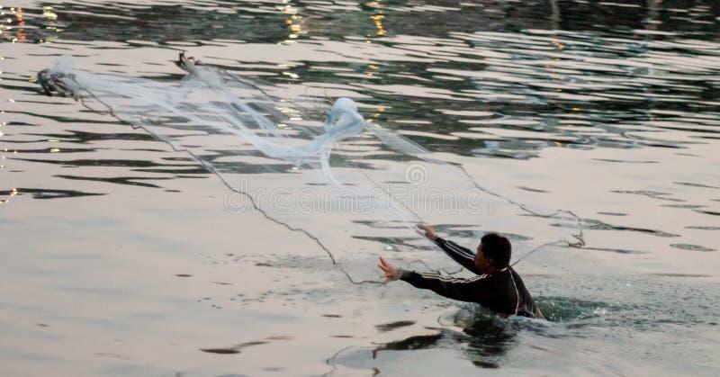 Niezidentyfikowany mężczyzna rzut sieć przy morzem obraz royalty free