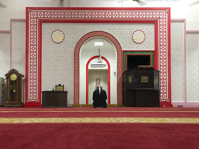 Niezidentyfikowany Muzułmański mężczyzna wewnątrz siedzi puszek w solat pozyci Masjid Muhammadiah, Ipoh, Perak zdjęcia stock