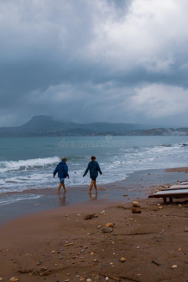 Niezidentyfikowany para spacer w piasku plaża z turkus wodą w chmurnym dniu obrazy royalty free