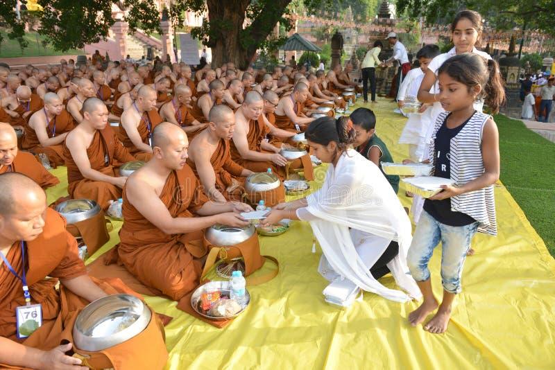 Niezidentyfikowanym mnichom buddyjskim dają karmowej ofiarze od ludzi przy Mahabodhi świątynny Bodh Gaya zdjęcie stock