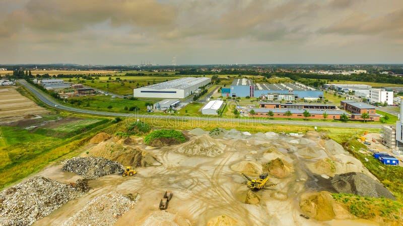 Nieznacznie alienujący widok z lotu ptaka park przemysłowy z magazynem dla materiałów budowlanych w przedpolu, wielka fabryka obraz royalty free