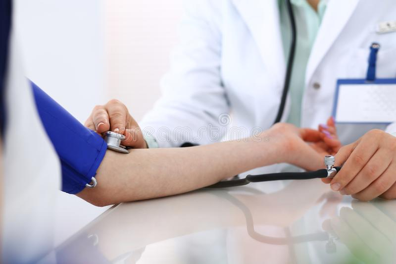 Nieznane doktorska kobieta sprawdza ciśnienie krwi żeński pacjent, w górę Kardiologia w medycyny i opieki zdrowotnej pojęciu obraz stock